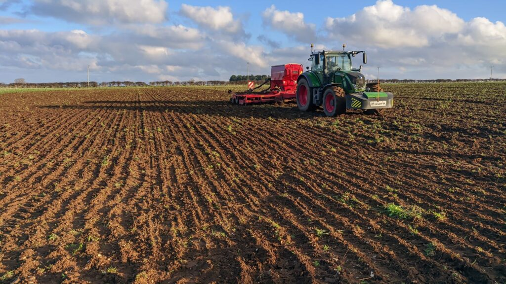 A tractor drilling wheat in a field