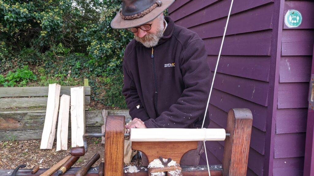 A man turns wood on a pole lathe